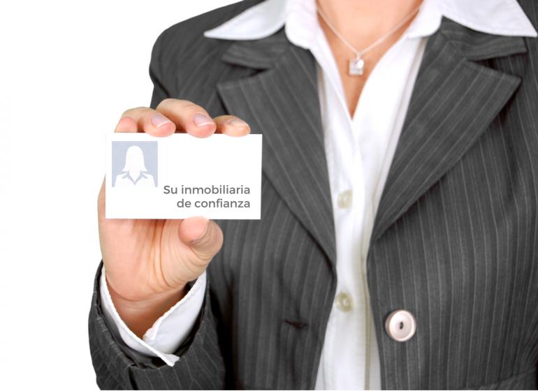 Agente inmobiliaria mostrando tarjeta de negocios
