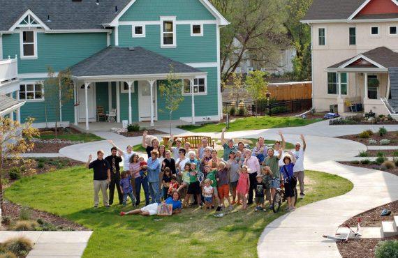 Foto grupal de familias en el centro de una plaza en una comunidad de cohousing