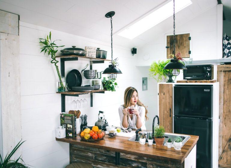 joven oriental sentada en cocina moderna de madera y hierro