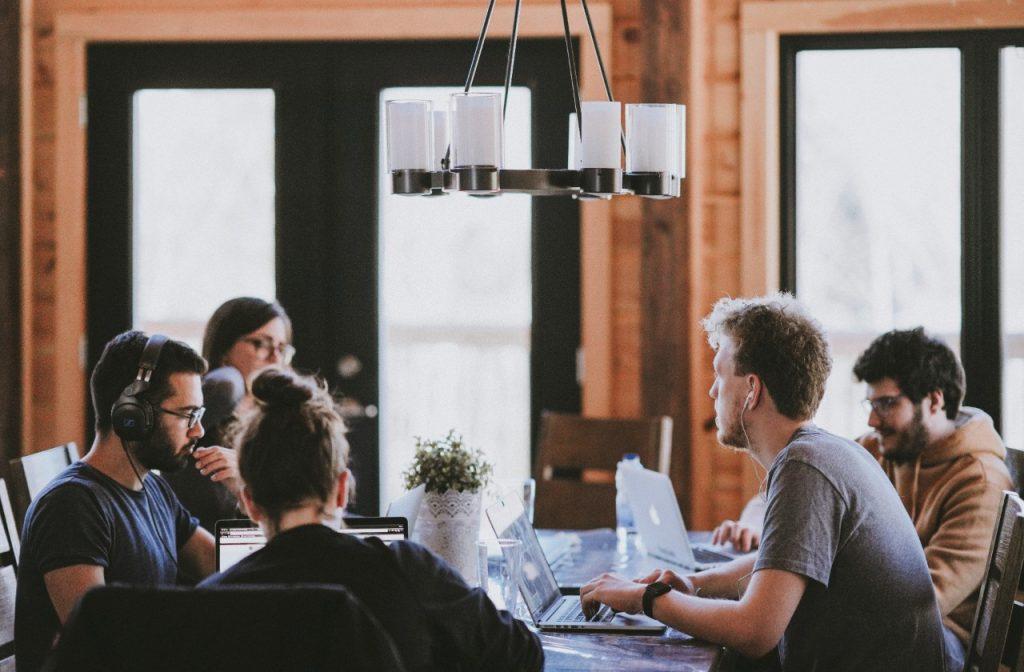 jóvenes millennials trabajando en sus computadoras portátiles alrededor de una mesa comunitaria de coworking