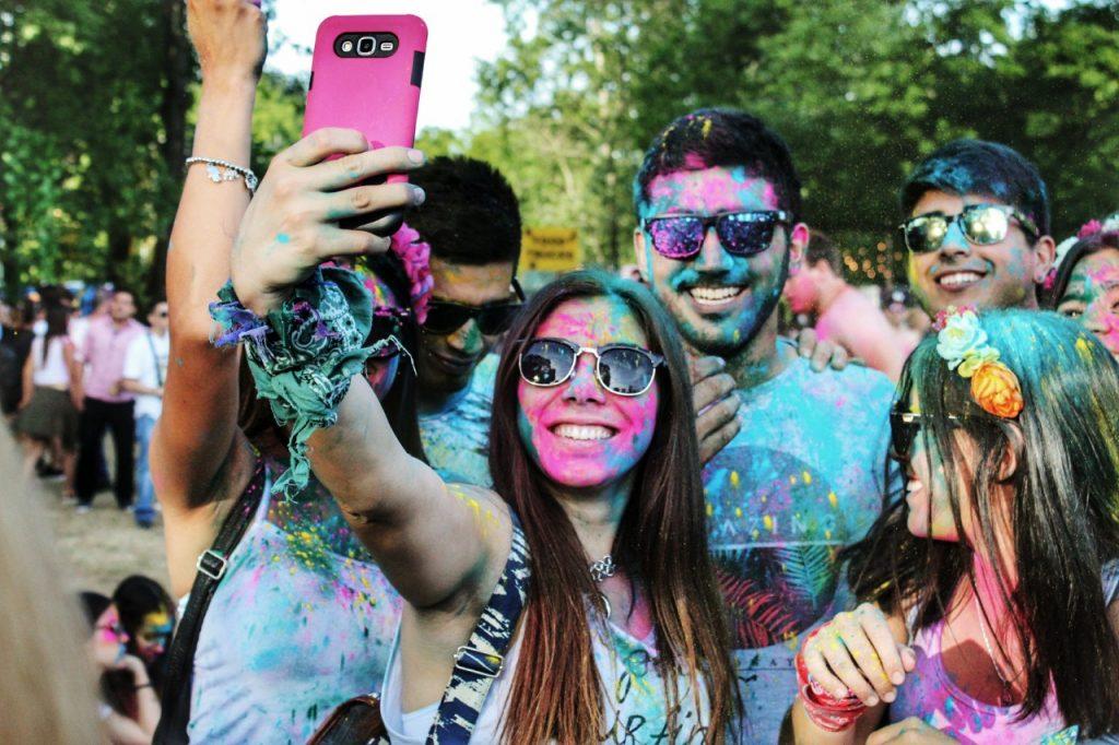 jóvenes millennials con gafas oscuras tomándose una selfie en el festival Holi