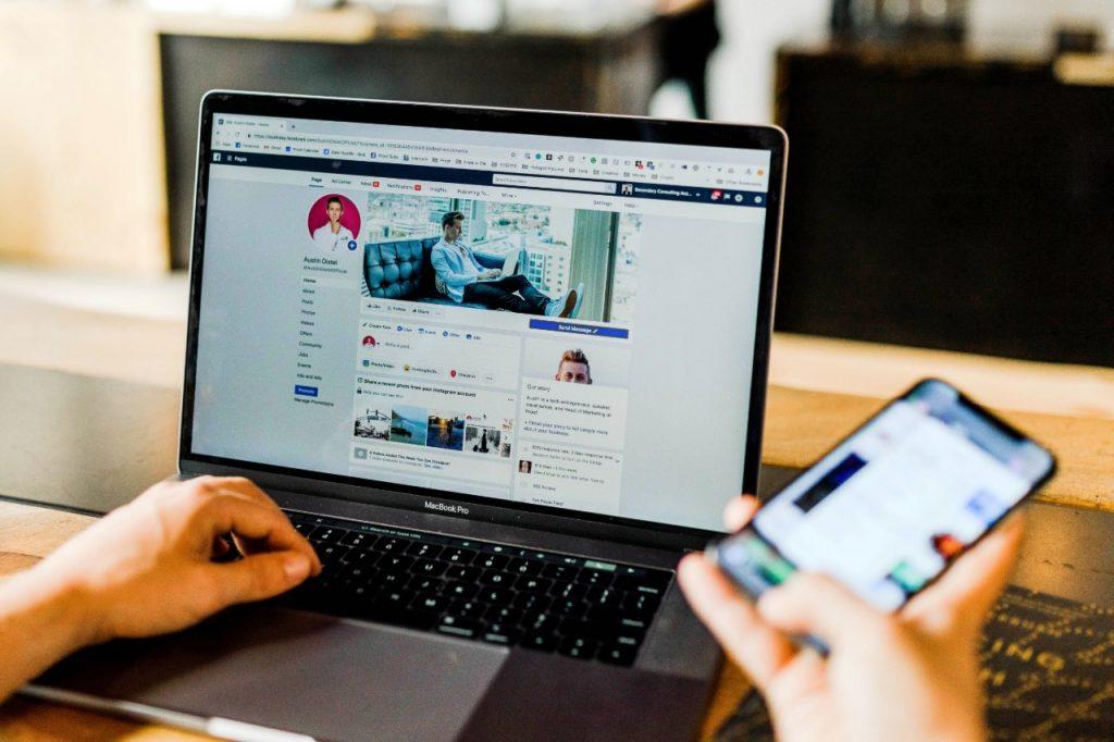 hombre joven chequeando Facebook en su computadora portátil MacBook Pro y en su celular