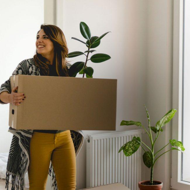 Mujer joven llevando caja en mudanza en departamento