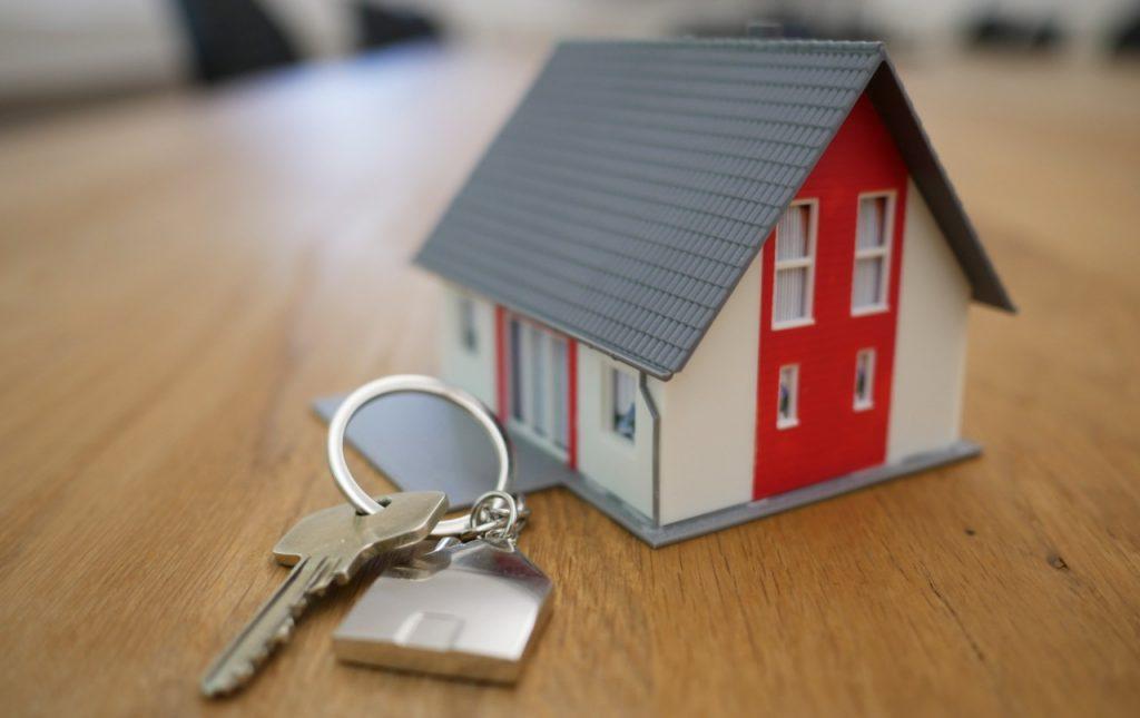 llaves y casa en miniatura sobre una mesa de madera